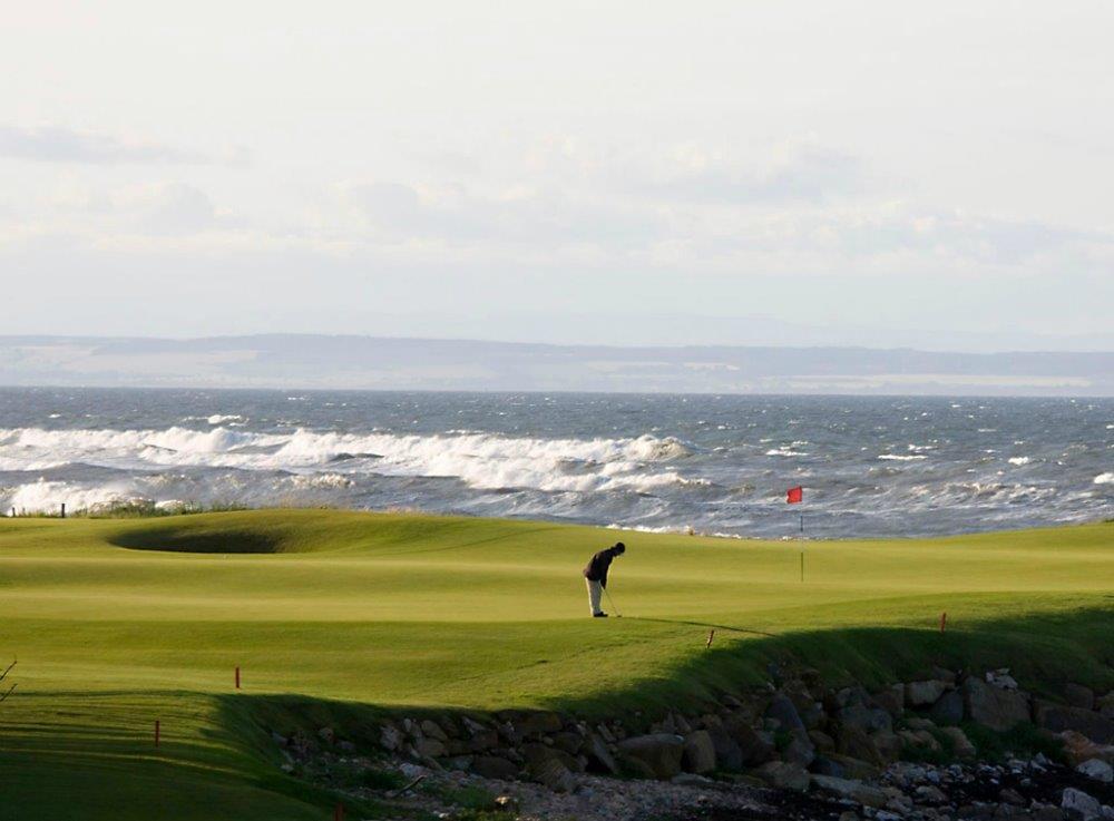Golfista en el campo de golf de Old Course de St Andrews en Escocia